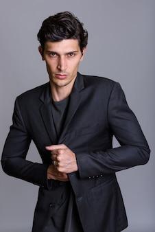 Студия выстрел молодого красивого бизнесмена, держащего куртку против