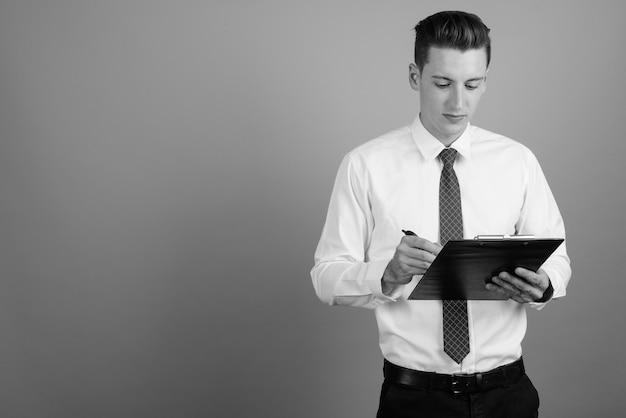 Студийный снимок молодого красивого бизнесмена в рубашке и галстуке на сером фоне в черно-белом