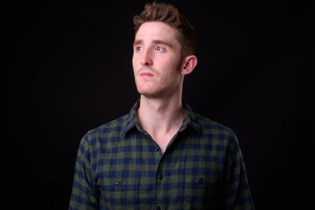 黒の背景に若いハンサムな流行に敏感な男のスタジオショット