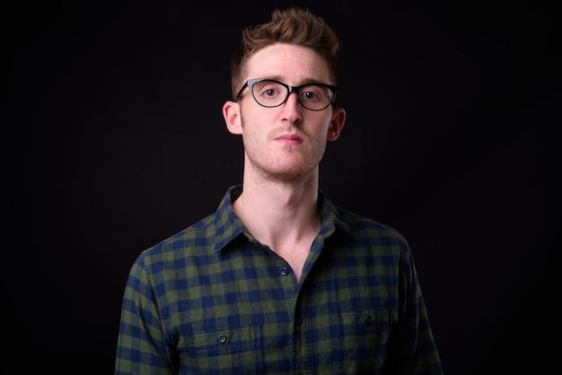 黒の背景に眼鏡をかけた若いハンサムな流行に敏感な男のスタジオショット