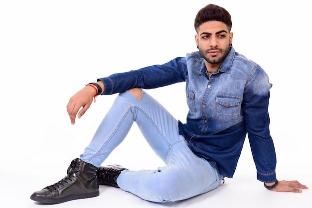 白い背景に対して隔離される床に座っている若いハンサムなインド人のスタジオ撮影