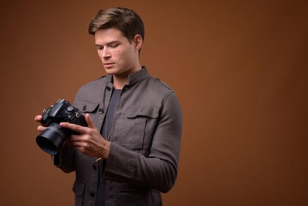 Студийный снимок молодого красивого человека как фотографа с камерой