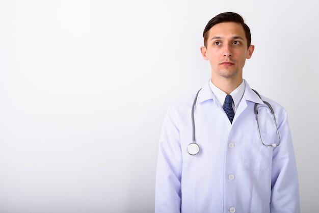 見ながら考えている若いハンサムな男の医者のスタジオショット