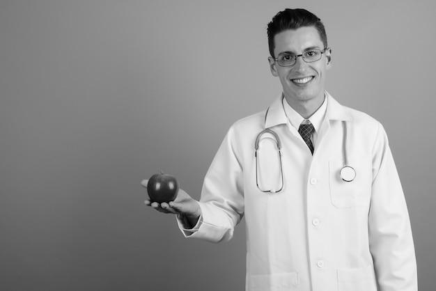 Студийный снимок молодого красавца-доктора в очках на сером фоне в черно-белом