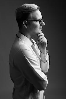 黒と白の灰色の壁にブロンドの髪を持つ若いハンサムな男の医者のスタジオショット
