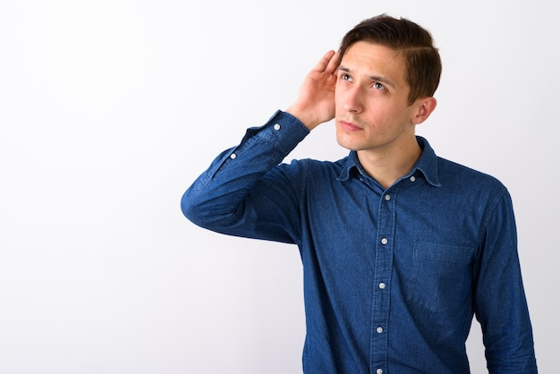 Студийный снимок молодого красивого человека, слушающего, снова думая
