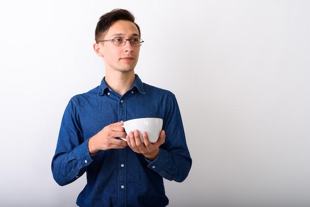 Студийный снимок молодого красивого человека, думающего, держа кофе