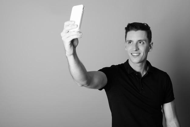 Студийный снимок молодого красивого человека, использующего мобильный телефон на сером фоне в черно-белом