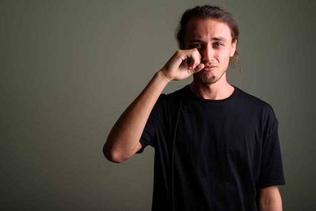 色付きの背景に黒いシャツを着ている若いハンサムな男のスタジオ撮影