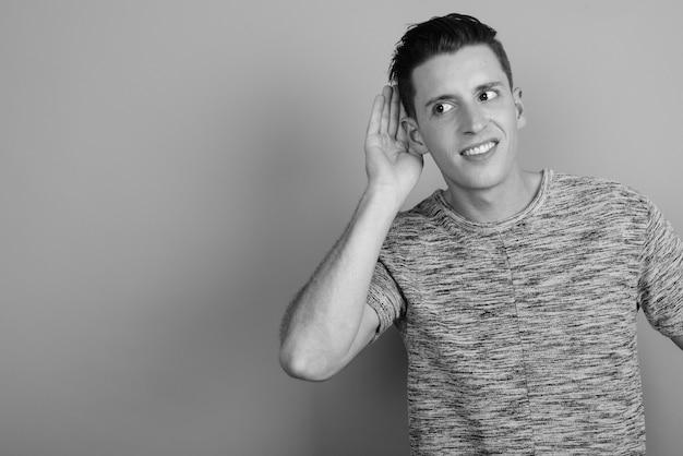 黒と白の灰色の背景に灰色のシャツを着ている若いハンサムな男のスタジオショット