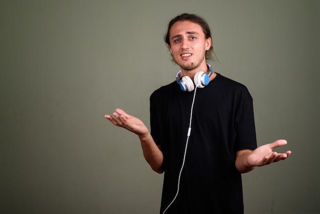 Студийный снимок молодого красивого человека в наушниках на цветном фоне