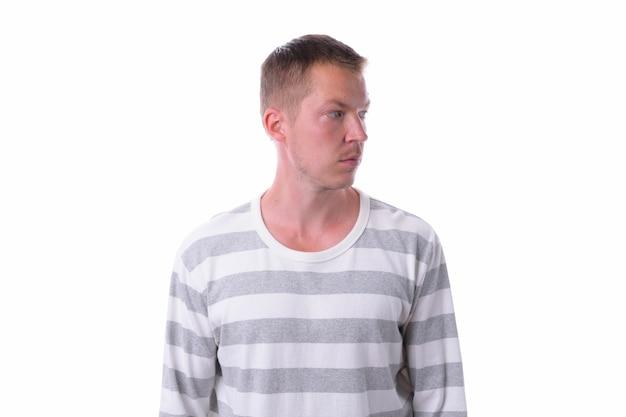 Студийный снимок молодого красавца в рубашке с длинными рукавами, изолированного на белом фоне