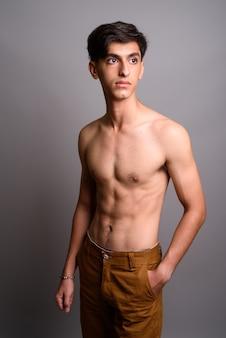 灰色の背景に対して上半身裸の若いハンサムなペルシャの10代の少年のスタジオ撮影