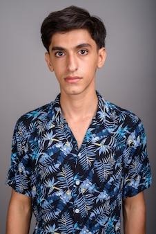 Студийный снимок молодого красивого персидского подростка в гавайской рубашке на сером фоне
