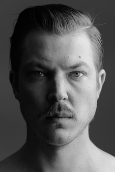 Студийный снимок молодого красивого скандинавского мужчины с усами без рубашки на сером в черно-белом
