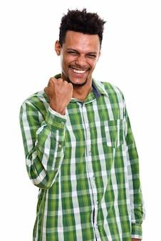 Студийный снимок молодого счастливого африканца, улыбающегося, выглядя мотивированным