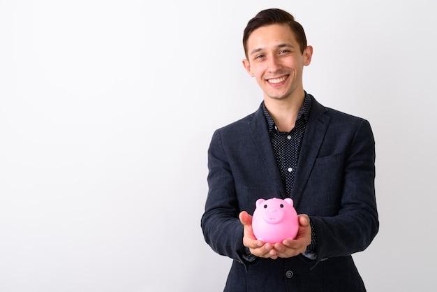 豚を保持しながら笑っている若い幸せな実業家のスタジオショット