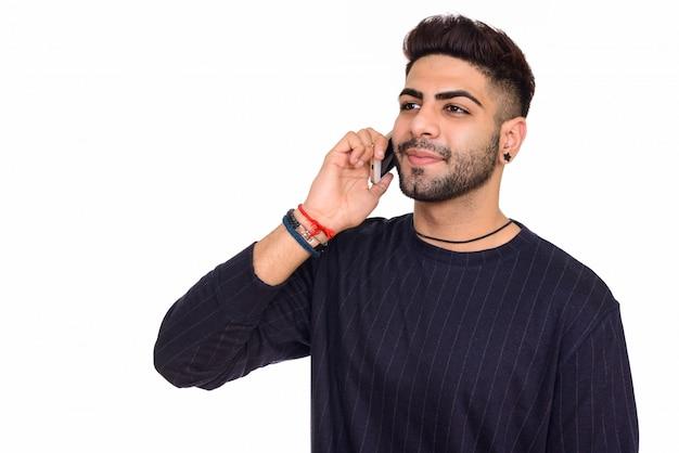 白い背景に対して隔離される携帯電話で話している若い幸せなインド人のスタジオ撮影