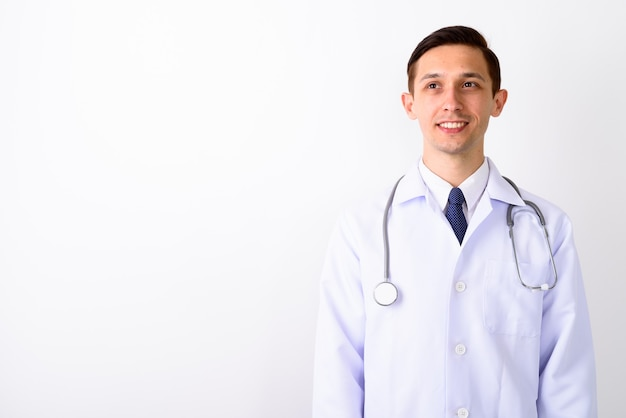 笑顔で考えながら若い幸せな男の医者のスタジオショット