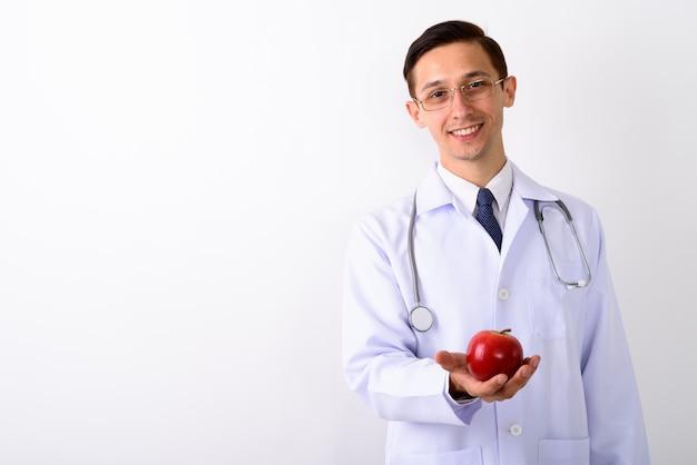 Студийный снимок доктора молодого счастливого человека, улыбающегося, держа красный