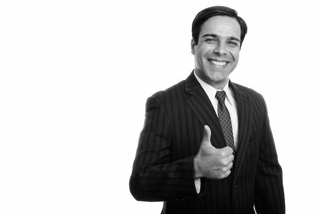 Студийный снимок молодого счастливого персидского бизнесмена, улыбающегося, давая изолированный палец вверх