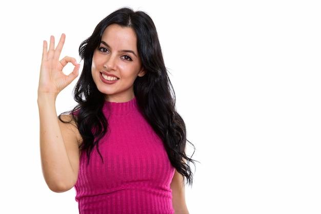 大丈夫を与えながら笑っている若い幸せなスペインの女性のスタジオショット