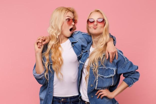 カジュアルな服装でピンクの背景の上に立っている間、お互いに楽しんで抱きしめている若い楽しい魅力的な長い髪のブロンドの双子のスタジオショット