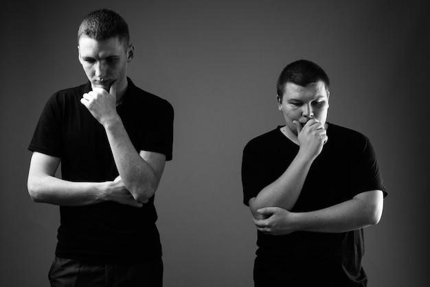 黒と白の黒い壁に対して一緒に若い男と太りすぎの若い男のスタジオショット