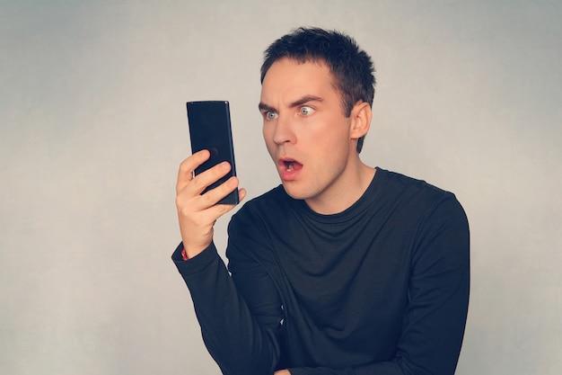 Студия выстрел молодого человека, использующего мобильный телефон, глядя в шоке на синем фоне. сильное удивление на лице симпатичного парня, читающего сообщение на современном смартфоне.