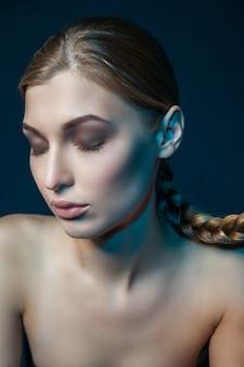 Студийный снимок молодой модели с закрытыми глазами, щекой и ухом, окрашенными в синий цвет.