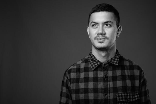 黒と白の灰色の壁に市松模様のシャツを着ている若い多民族のアジア人男性のスタジオショット