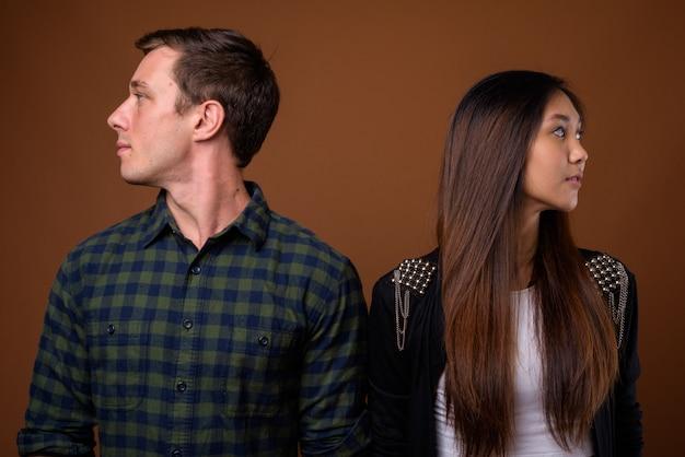 茶色の壁に若い多民族のカップルのスタジオ撮影