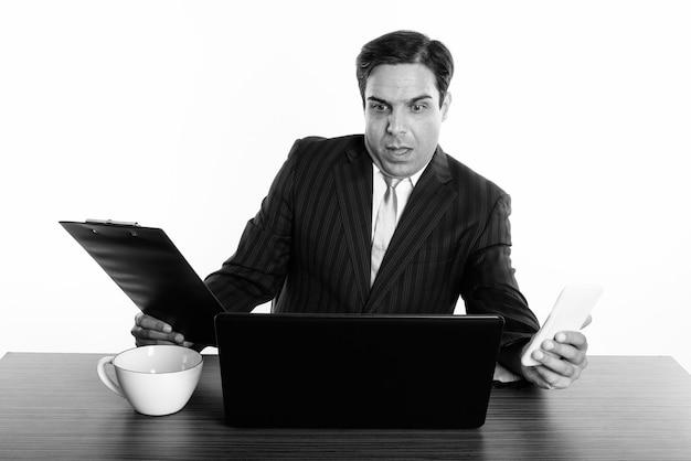 Студийный снимок молодого персидского бизнесмена, сидящего за деревянным столом, изолированные, черно-белые