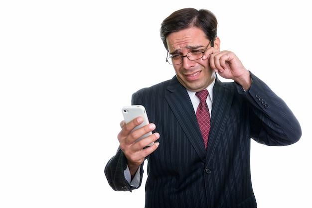 Студийный снимок молодого персидского бизнесмена с помощью мобильного телефона