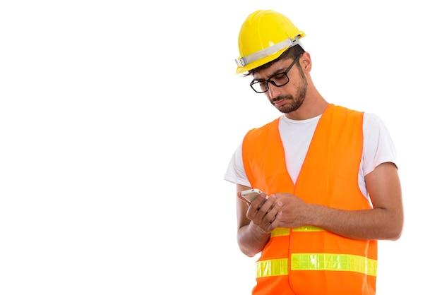 모빌을 사용하여 젊은 페르시아 남자 건설 노동자의 스튜디오 샷