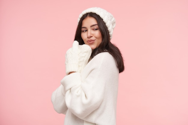ピンクの壁の上に立っている間、彼女の顔に手袋で手を上げ、唇をふくれっ面する白いニットの服を着た若いポジティブブルネットの女性のスタジオショット