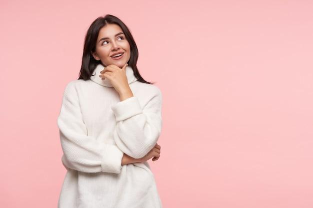 Студийный снимок молодой красивой брюнетки с распущенными волосами, касающейся ее лица поднятой рукой, мечтательно смотрящей вверх, стоящей над розовой стеной