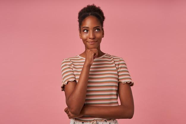 Студийный снимок молодой симпатичной брюнетки, держащей поднятой рукой подбородок, положительно смотрящей в сторону, стоящей над розовой стеной