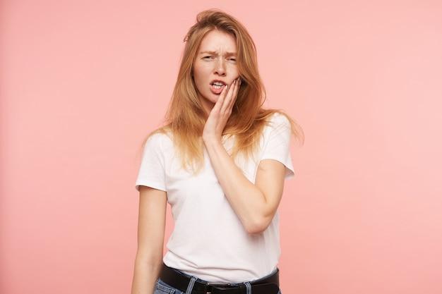 ピンクの背景の上に分離された、彼女の顔に手のひらを保ち、カメラを見ながら目を細めている自然なメイクの若い赤毛の女性のスタジオショット