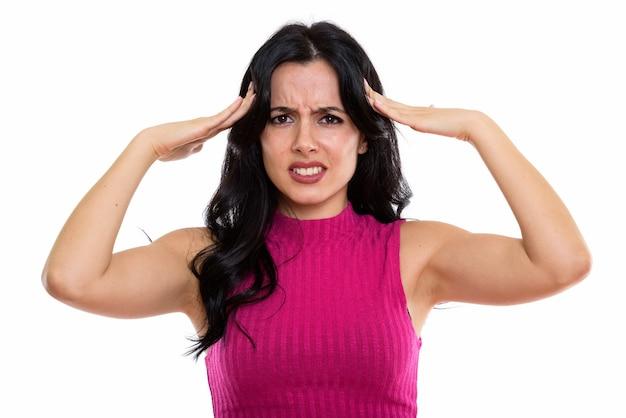 Студийный снимок молодой подчеркнутой испанской женщины с головной болью