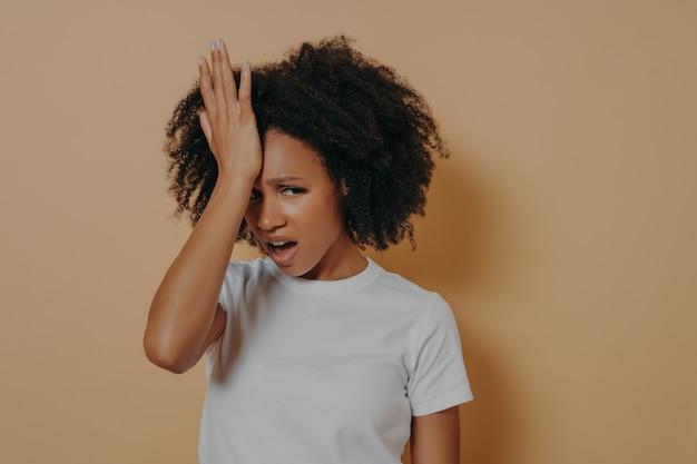 강한 두통이나 머리 편두통으로 고통받는 이마에 손을 대고 스트레스를 받는 젊은 아프리카 여성의 스튜디오 샷, 모래색 배경에서 격리된 불쾌한 얼굴 표정으로 카메라를 바라보고 있습니다