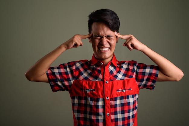 色に対して赤い市松模様のシャツを着ている若い10代の男のスタジオ撮影