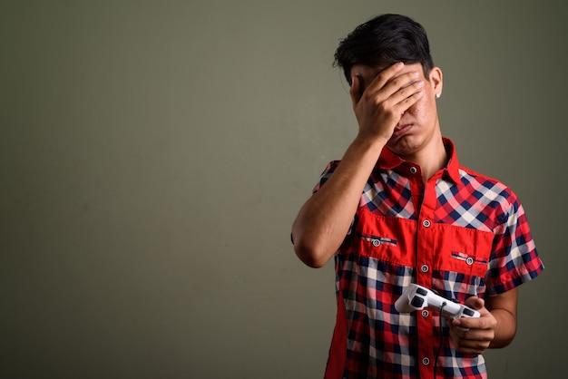 Студийный снимок молодого человека-подростка в красной клетчатой рубашке на фоне цветных