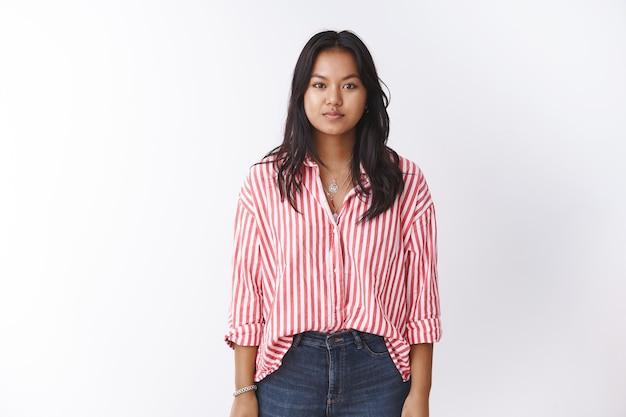 ピンクのストライプのブラウスとジーンズの若いベトナム人女性のスタジオショットは、カメラの焦点を合わせて見つめながらリラックスして立って、白い壁にポーズをとってカジュアルな表情で腕を横に保持します