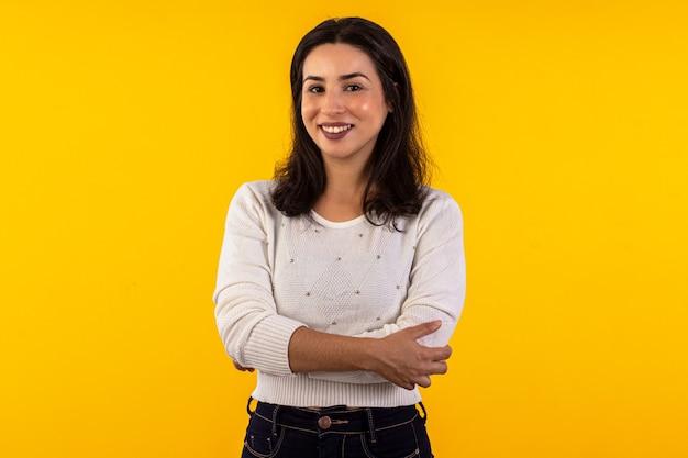 다양한 표정으로 노란색 배경에 흰색 셔츠를 입은 젊은 여성의 스튜디오 샷