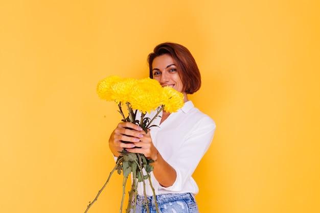 黄色の背景にスタジオ撮影カジュアルな服を着て幸せな白人女性の短い髪白いシャツと黄色のアスターの花束を保持しているデニムパンツ