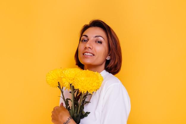 Студия выстрелил на желтом фоне счастливая кавказская женщина с короткими волосами в повседневной одежде, белая рубашка и джинсовые брюки, держит букет желтых астр