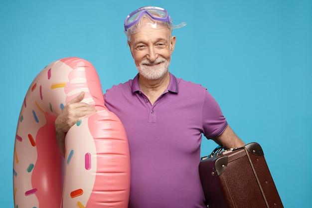 Studio shot of overjoyed cheerful elderly mature male with beard posing isolated with snorkeling mask