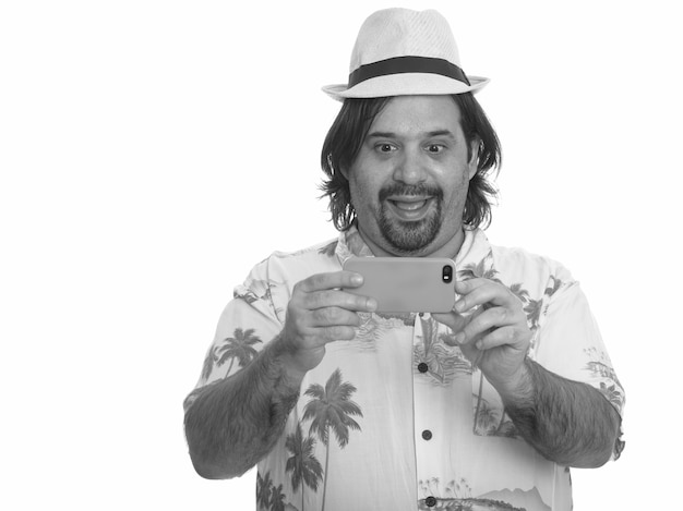 Studio shot of overweight bearded tourist man ready for vacation isolated against white background in black and white
