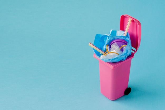 Studio shot of a pink big trash on blue background